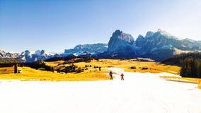 Snowboarding dos povos e esqui abaixo das montanhas dos cumes da dolomite em Val Gardena, Itália imagens de stock royalty free