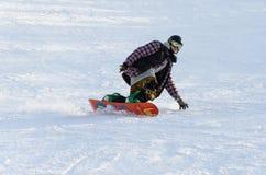 Snowboarding för ung man ner pisten Royaltyfria Foton