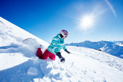 Snowboarding fail. Female snowboarder wearing colorful helmet, blue jacket, grey gloves and pink pants falling off on her knees and wrists on ski resort piste Stock Image