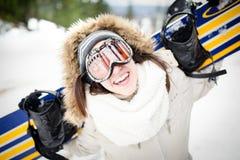snowboarding Giovane bella donna con la passamontagna che tiene il suo snowboard alla giovane donna del pendio dello sci nella st Immagine Stock