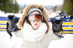 snowboarding Giovane bella donna con la passamontagna che tiene il suo snowboard alla giovane donna del pendio dello sci nella st Fotografia Stock