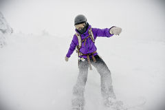 Snowboarding Girl in Blizzard. A female snowboarder in her protective equipment experiencing a complete blizzard white out Royalty Free Stock Photos