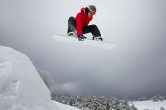 Snowboarding jump. Snowboarder in red clothes jumping from springboard Stock Images