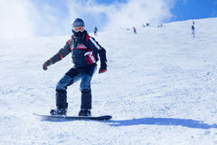 Snowboarding on the mountain. Snowboarder in action at the mountains Royalty Free Stock Image