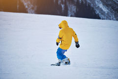 Snowboarding in mountains ski resort. Back view of snowboarder in bright yellow jacket and blue pants rides down on snow slope at sunny winer day in mountain ski Royalty Free Stock Image