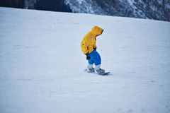 Snowboarding in mountains ski resort. Snowboarder in bright yellow parka and blue pants looks down on snow slope before start to ride at sunny winer day in Stock Photos
