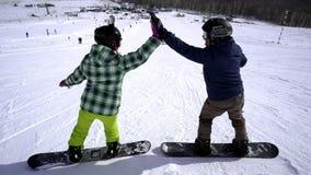 Snowboarding na estância de esqui dois amigos cumprimentam-se e começam-se montar em uma inclinação nevado filme