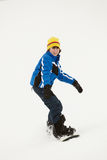 A snowboarding nova do menino inclina-se para baixo no feriado Foto de Stock Royalty Free