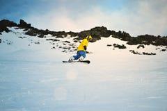 Snowboarding på solnedgången i berg Arkivfoton