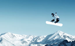 Snowboarding. Snowboarder making jump high in clear sky Stock Photos