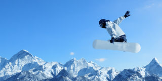 Snowboarding. Snowboarder making jump high in clear sky Stock Images