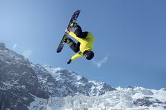 Snowboarding sport. Snowboarder making high jump in clear blue sky Royalty Free Stock Image