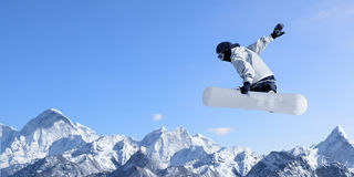 Snowboarding sport. Snowboarder making high jump in clear blue sky Stock Images