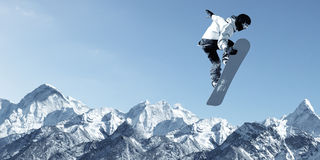 Snowboarding sport. Snowboarder making high jump in clear blue sky Stock Image