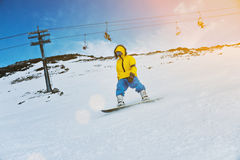 Snowboarding at sunset in mountains Stock Photo
