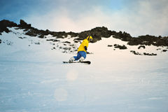 Snowboarding at sunset in mountains. Man rides his snowboard on ski slope in winter mountains, in ski resort Sunset time, dramatic weather and light leaks comes Stock Photos