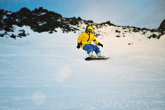Snowboarding at sunset in mountains Stock Image