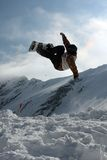 Snowboarding trick. Snowboarder in the mountains performing a jump Royalty Free Stock Images