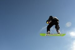 Snowboarding trick. Snowboarder in the mountains performing a jump Royalty Free Stock Photo