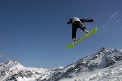 Snowboarding trick. Snowboarder in the mountains performing a jump Royalty Free Stock Photos