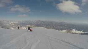 Snowboarding very fast down the slope, beautiful snowy mountain landscape in the background, extreme winter sport stock footage