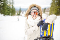 Snowboarding.Young beautiful woman with ski mask holding her snowboard at ski slope Young woman in ski resort Royalty Free Stock Photo