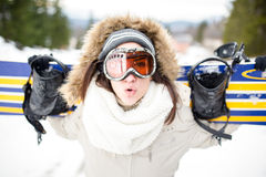 Snowboarding.Young beautiful woman with ski mask holding her snowboard at ski slope Young woman in ski resort Stock Photography