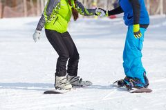Snowboarding. Young couple snowboarders in a ski resort. unrecognizable Stock Photos
