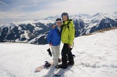 Snowboardingspaar in greep op de bovenkant van berg stock foto's