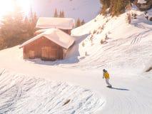 Snowboardist su un pendio dello sci alla capanna alpina il giorno soleggiato, alpi Fotografie Stock Libere da Diritti