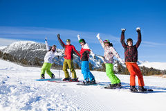 Snowboards, skies standing lifting hands up Stock Image