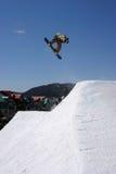 Snowboardsprung auf blauem Himmel Stockbild