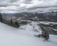 Snowborder, das Schnee auf Piste zerschneidet Stockfotografie