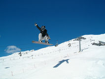 Snowborder (girl) jumping. Snowboarder jumping in the air in Italy Alps Stock Photo