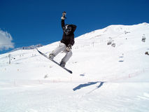 Snowborder (girl) jumping. Snowboarder jumping in the air in Italy Alps Royalty Free Stock Photo
