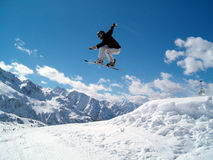Snowborder (girl) jumping. Snowboarder jumping in the air in Italy Alps Royalty Free Stock Images