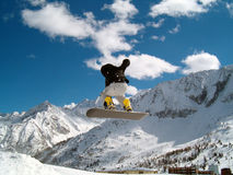 Snowborder (girl) jumping. Snowboarder jumping in the air in Italy Alps Stock Image