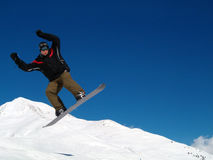 Snowborder jumping. Snowboarder jumping in the air in Italy Alps Stock Images
