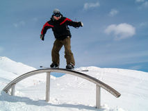Snowborder on the ramp. Snowboarder riding on the ramp in Snowpark Stock Photo