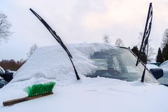 On the snowbound car hood lies a green brush. stock photo