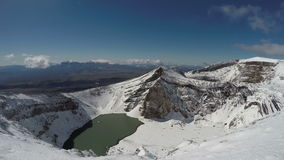Snowbound craters and a crater lake of active Gorely Volcano on Kamchatka Peninsula stock video