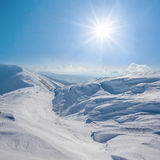 Snowbound hills under a sparkle sun Royalty Free Stock Photo