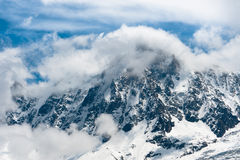 Snowbound mountain peaks in Alps. Snowbound mountain peaks in clouds. High Alps Royalty Free Stock Photography