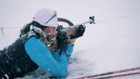 Snowbound shooting zone with a female biathlete firing