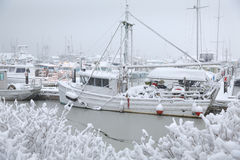 Snowbound Steveston Harbor, Richmond, British Colu. A lone fishboat tied to the dock waiting out a winter snowstorm. Steveston, British Columbia, Canada Royalty Free Stock Photo