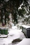 Snowbound walkway with  garbage bins Royalty Free Stock Photos