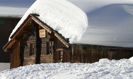 Snowbound wooden chalet. With lots of snow on its roof Stock Images