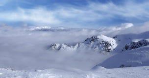 Snowcapped berg under blå himmel- och vitmolnen under dag Arkivbild
