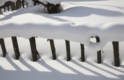 Snowcapped fence and shadow Royalty Free Stock Photo
