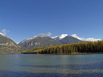 Snowcapped Mountains and Lake. This image of the Swan Range of mountains clad in snow and the lake with the golden tamaracks on shore was taken in western MT Stock Image